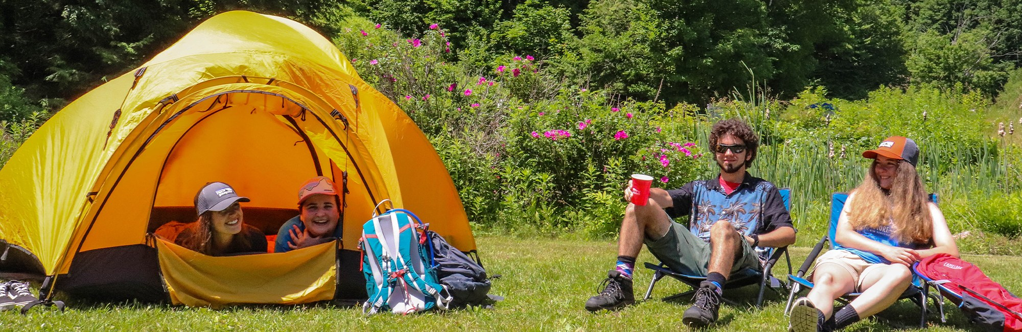 Yellow tent with people camping